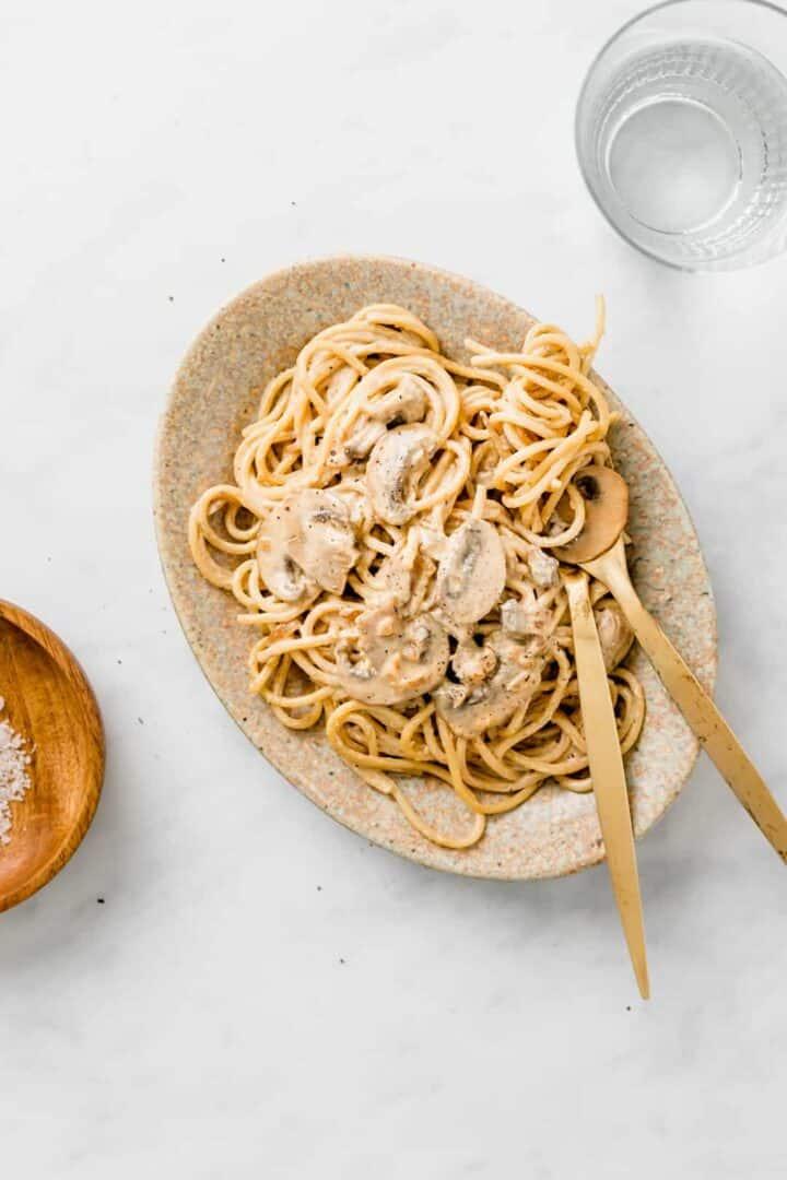 vegan pasta carbonara served on a brown plate