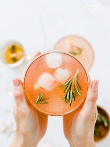 zwei hände halten einen grapefruit cocktail