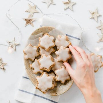 a hand grabbing german zimtsterne christmas cookies