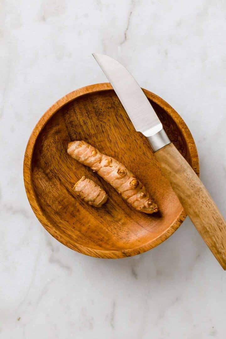 frische kurkuma wurzel in einer braunen schale neben einem messer