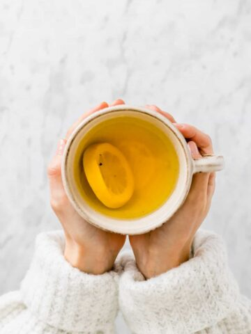 two hand holding a cup of ginger turmeric tea