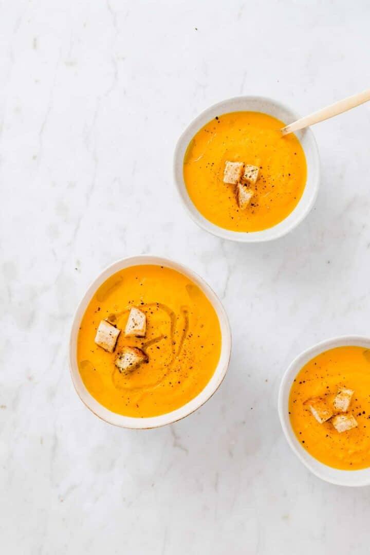 karotten orangen suppe in schalen mit croutons als topping