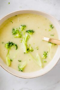vegan broccoli potato soup served in a bowl with a golden spoon