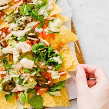eine hand greift nach nachos