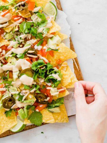 a hand grabbing vegan nachos