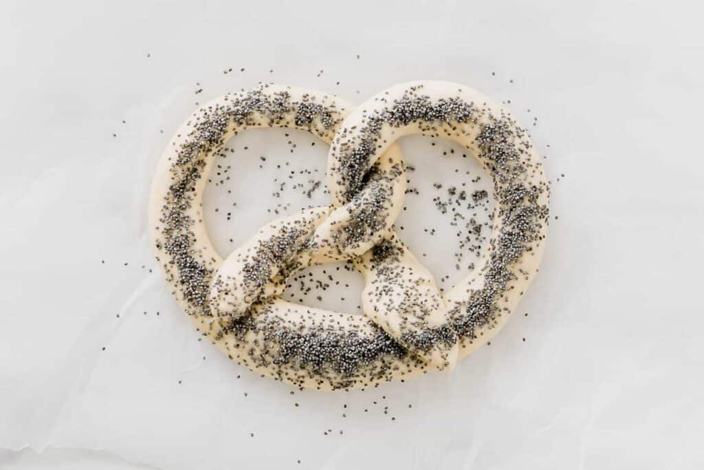 raw pretzel dough sprinkled with poppy seeds