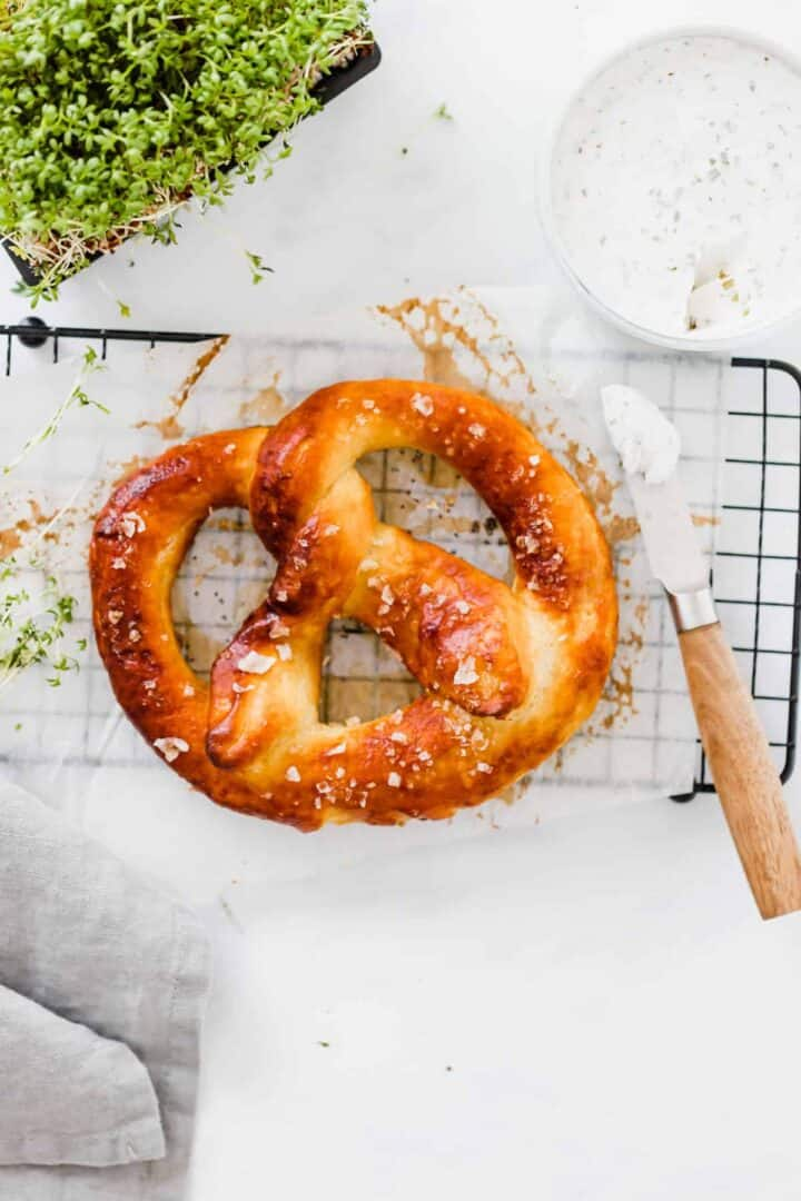 vegan pretzel on a black tray next to garden cress