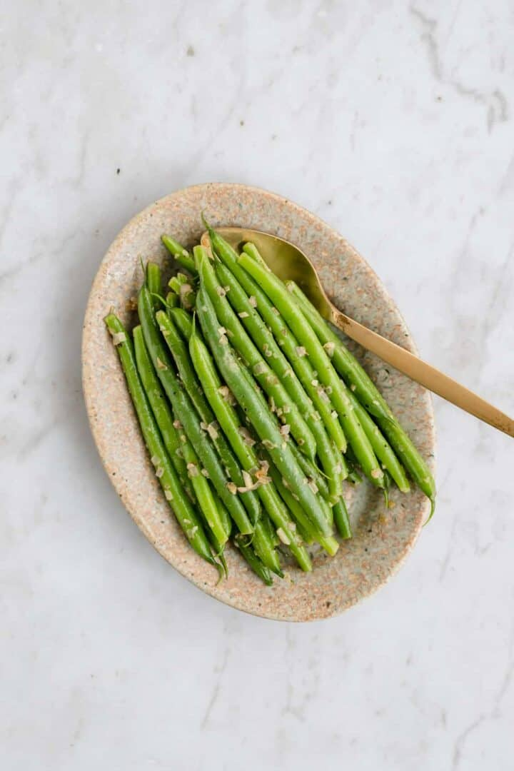 cooked green beans with garlic and shallots served on a plate