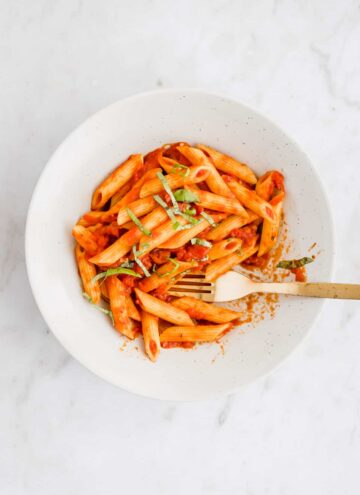 penne arrabiata serve in a plate with a golden fork
