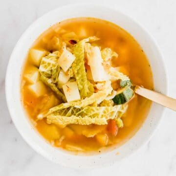 selbstgemachte gemüsesuppe in einer schale mit einem goldenen löffel