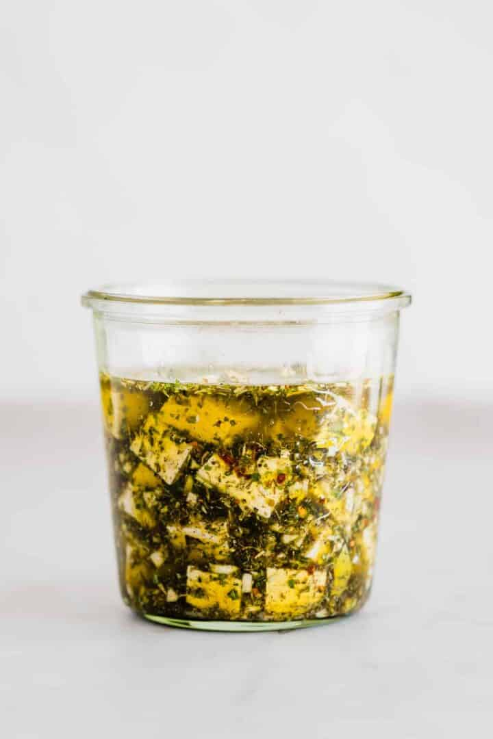 vegan tofu feta with olive oil and herbs in a mason jar