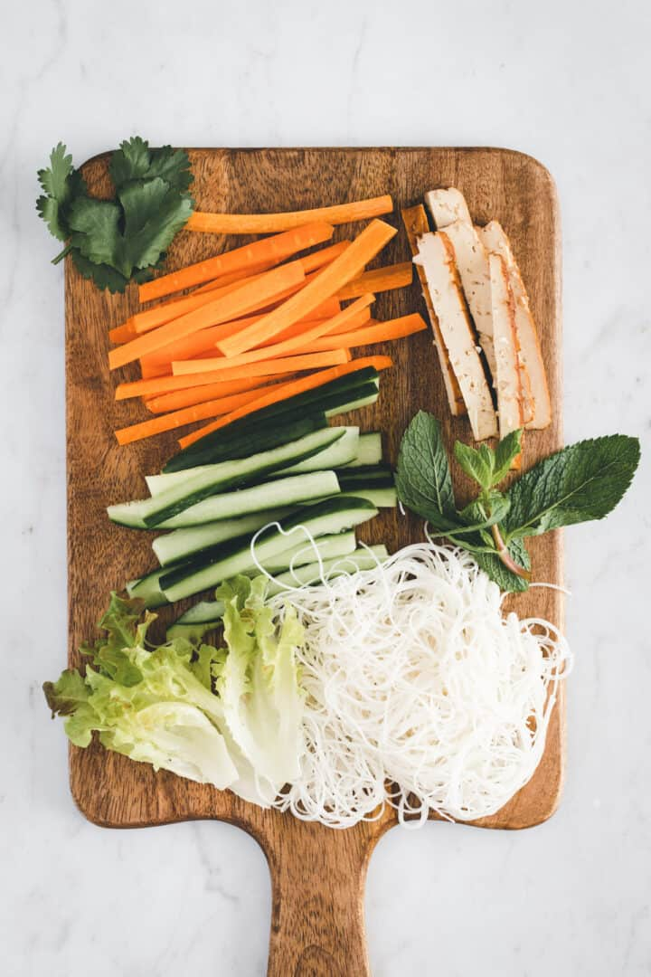 ingredients for vegan summer rolls on a cutting board