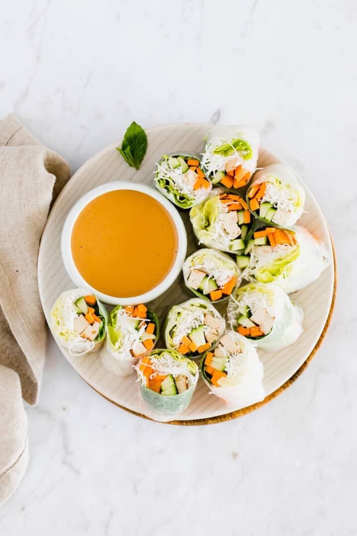 a plate with vietnamese summer rolls and peanut dipping sauce