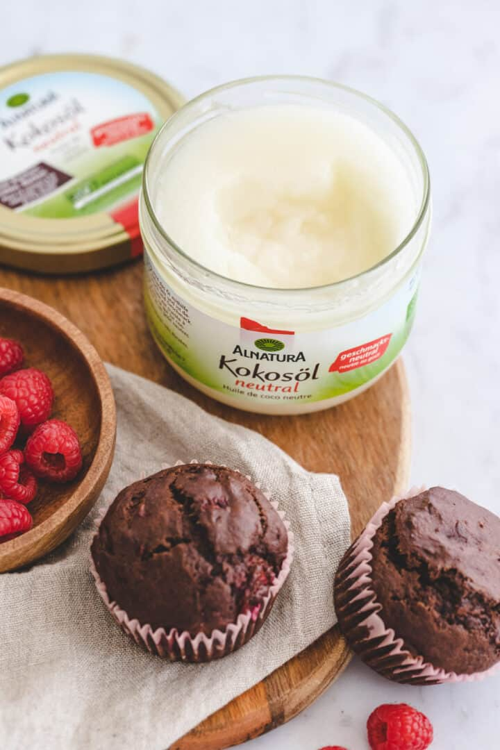 schokoladenmuffins mit himbeeren neben einem glas kokosöl