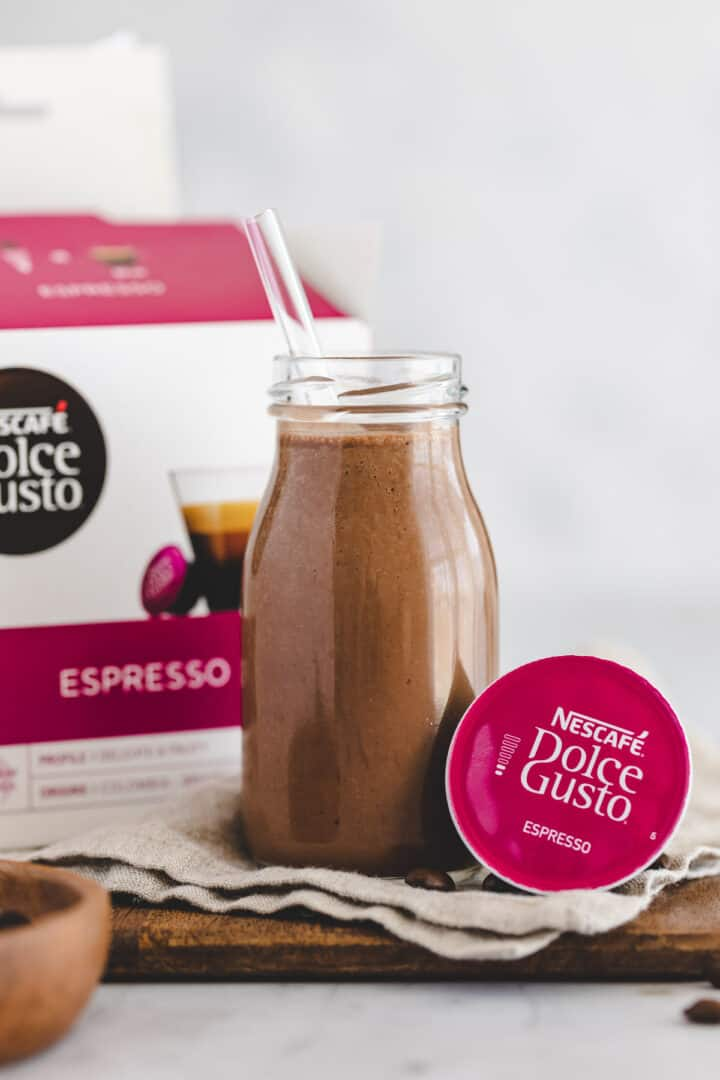coffee banana breakfast smoothie next to a box of dolce gusto capsules