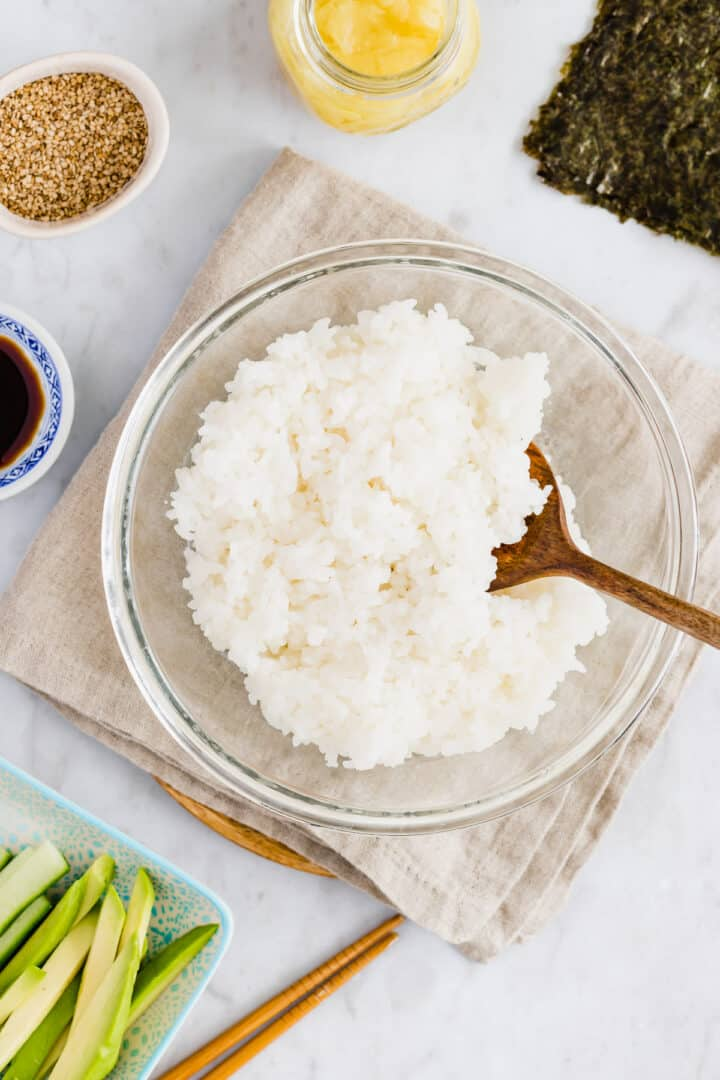 cooked sushi rice in a glass bowl next to sushi ingredients