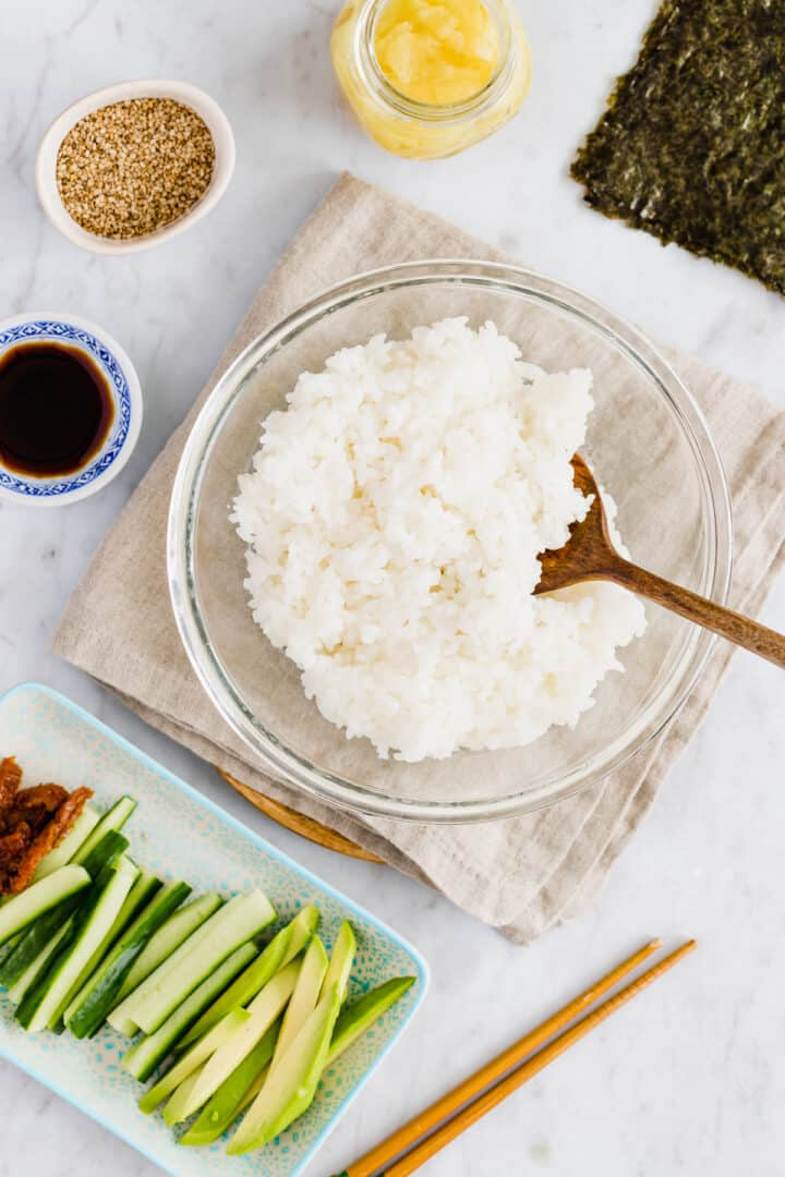 homemade sushi rice in a bowl next to ingredients for sushi