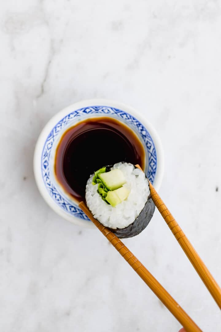 two chopsticks dipping a sushi into soy sauce