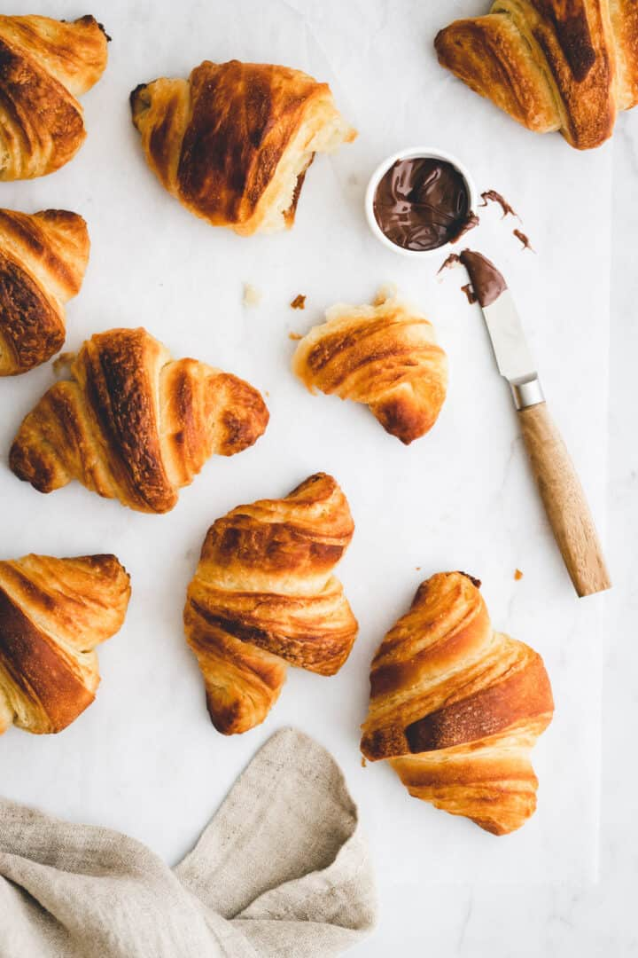 a table with vegan croissants next to a bowl of chocolate spread and a knife