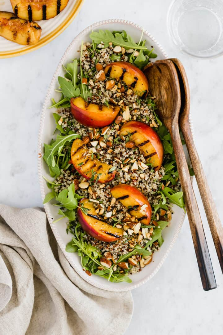 a plate with grilled peach salad, quinoa, and arugula