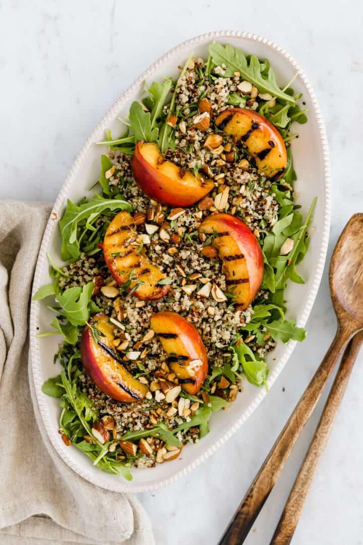 eine servierplatte mit quinoa salat, gegrilltem pfirsich, und rucola