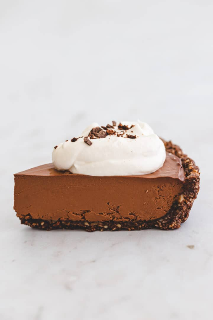 a piece of chocolate pie with dairy free whipped cream on top