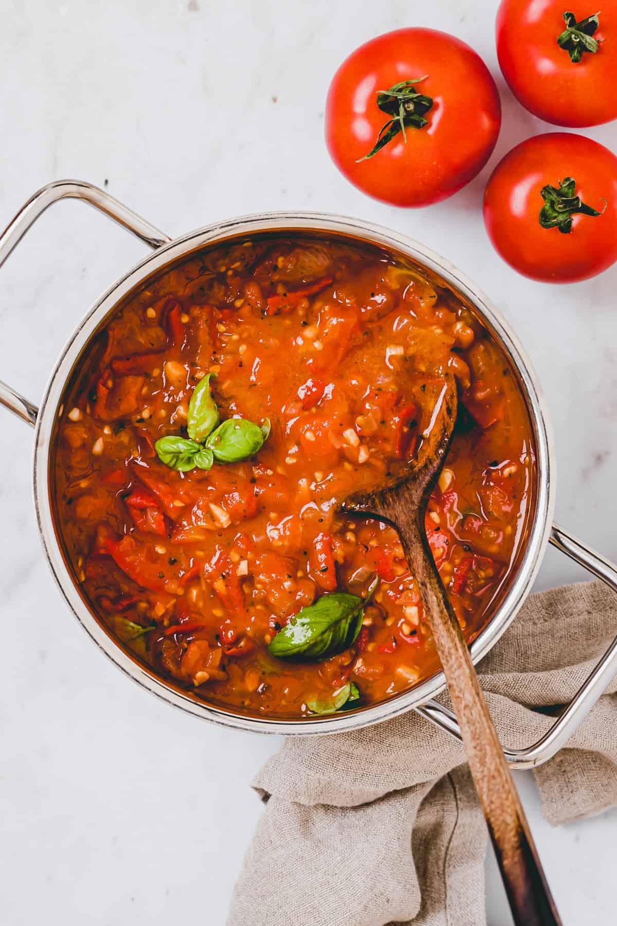 frisch eingekochte tomatensauce in einem topf neben tomaten