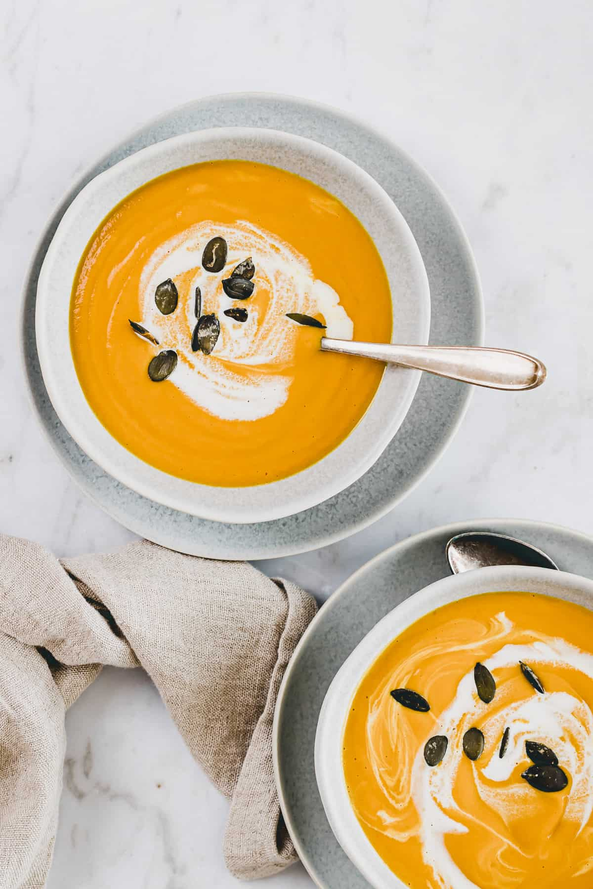 soup with pumpkin and ginger in two blue bowls