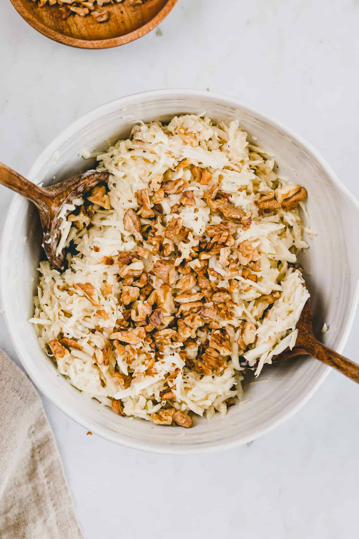 celeriac salad in a large bowl topped with walnuts