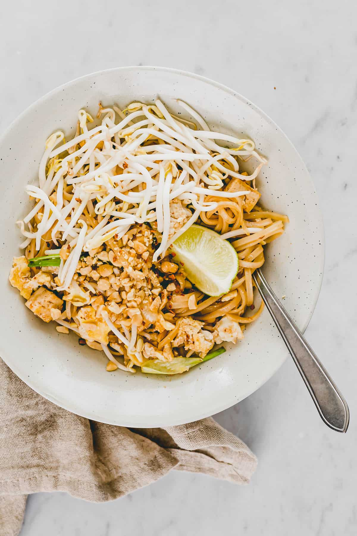 vegetarian pad thai noodles in a bowl topped with bean sprouts, lime, and peanuts