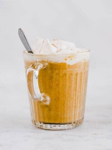 kürbis latte mit schlagsahne und zimt in einer glastasse