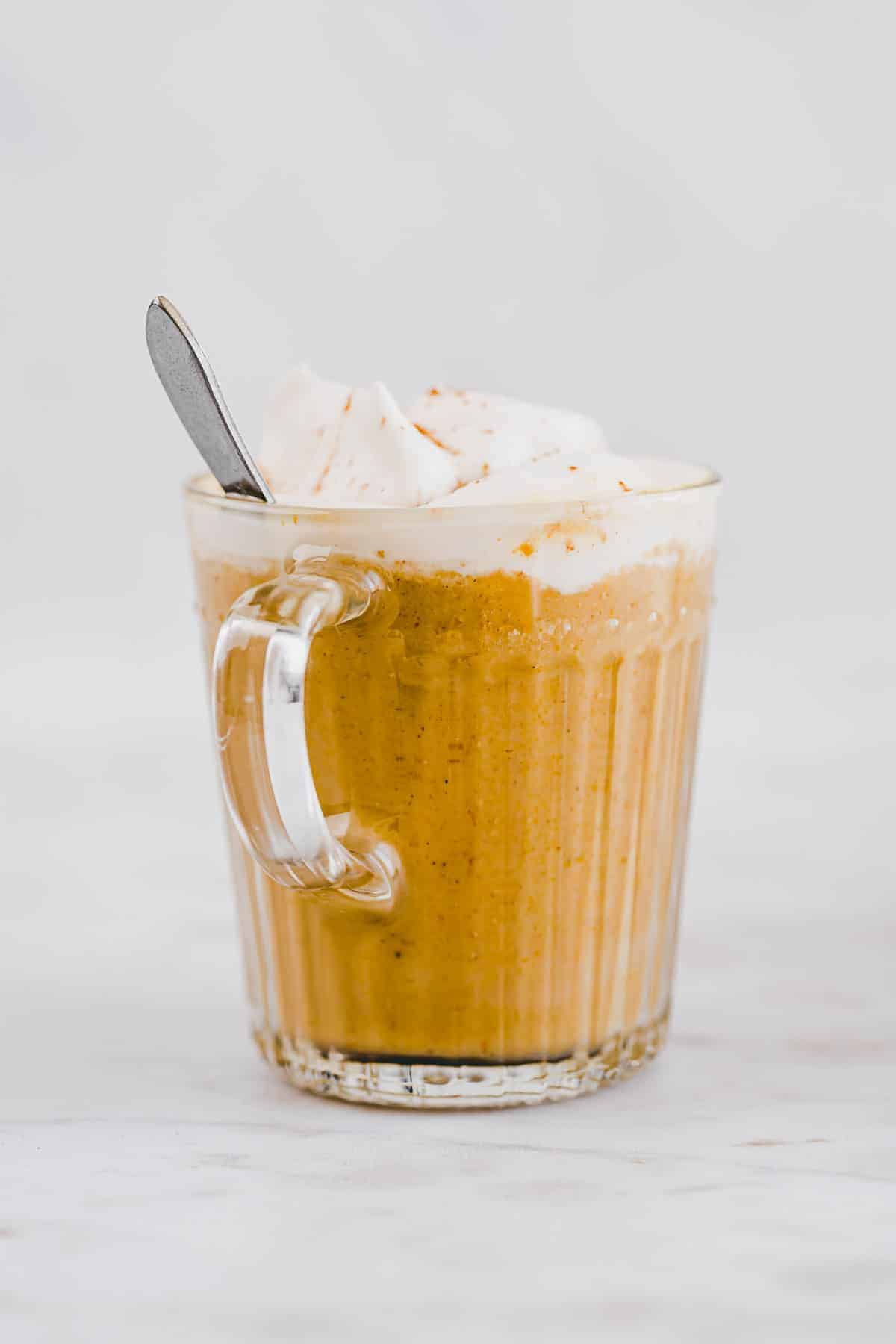 pumpkin spice latte with dairy-free whipped cream in a glass mug