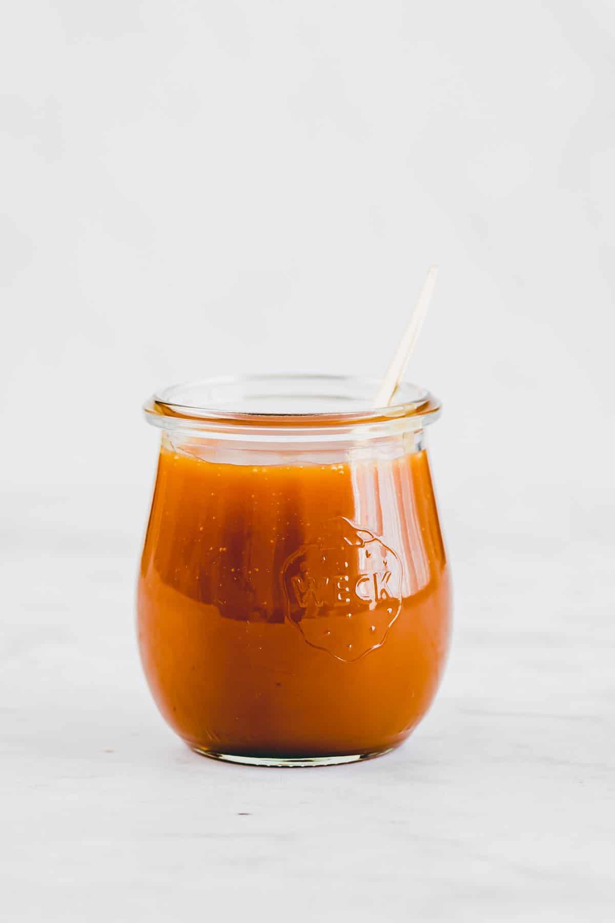 ein weck glas mit karamellsauce gefüllt und einem goldenen teelöffel