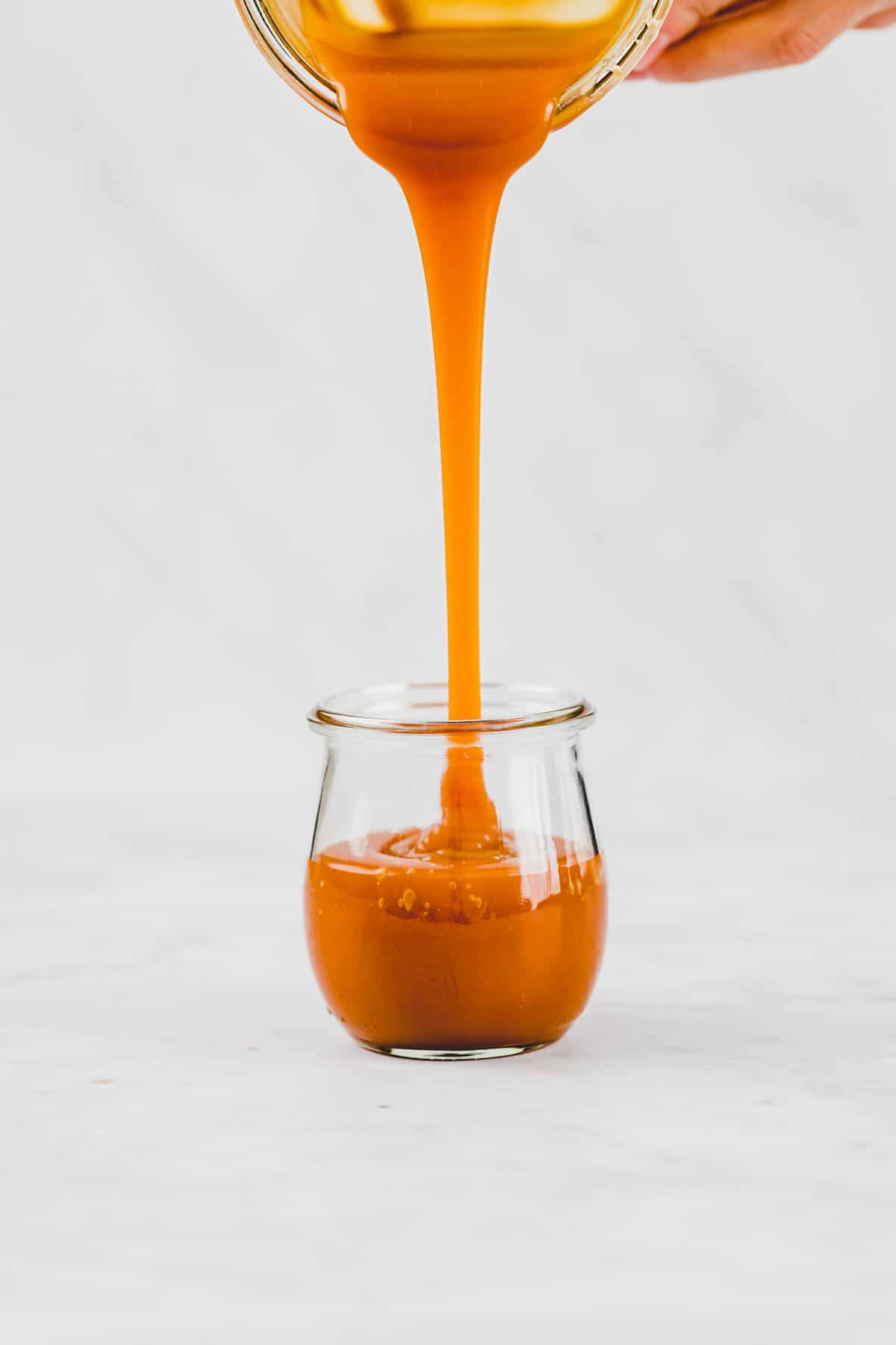pouring dairy-free caramel sauce into a tulip jar