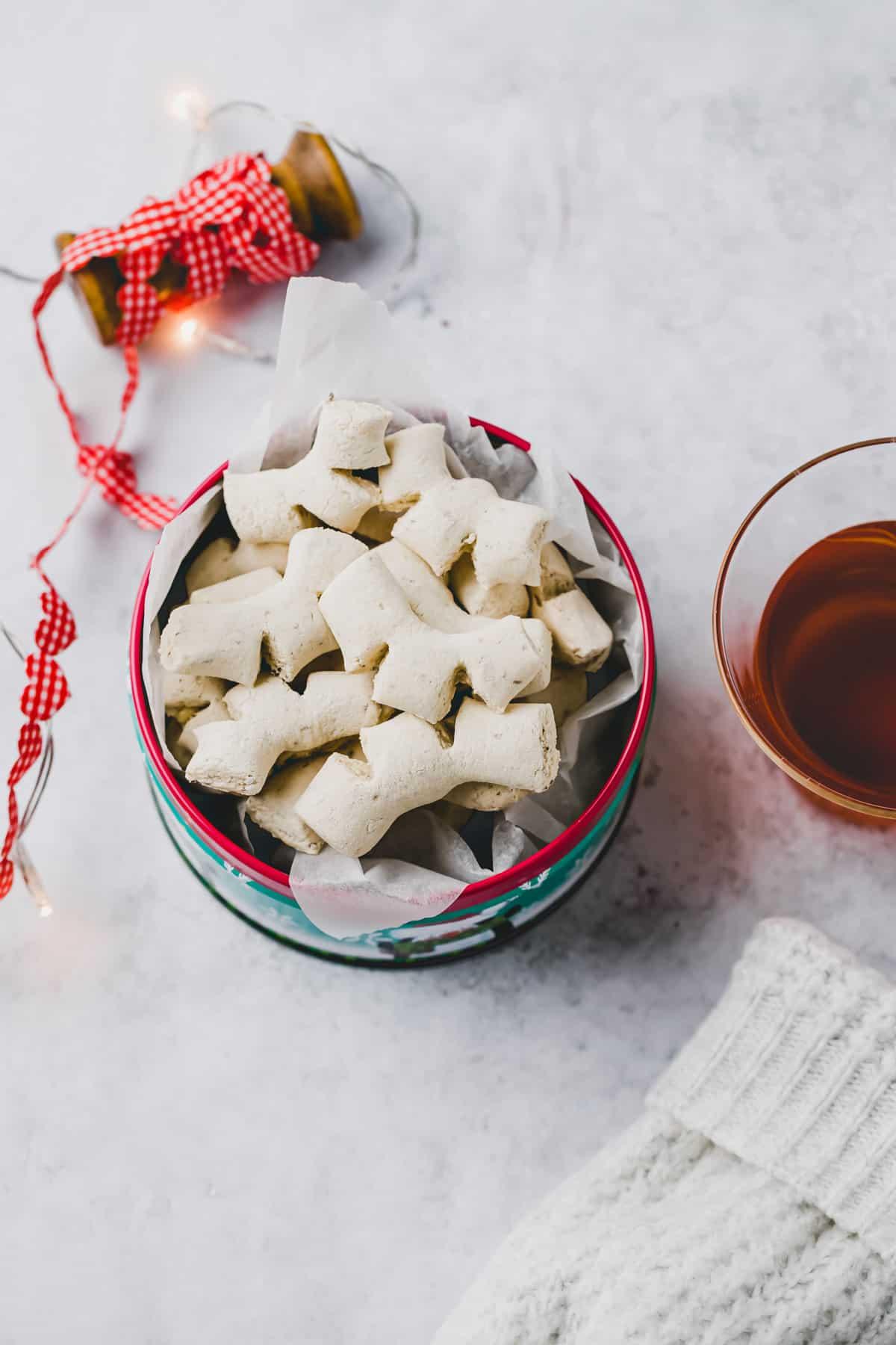 anise guetzli (chräbeli) in einer keksdose neben einer tasse tee