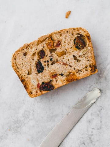 a slice of fruit bread next to a knife