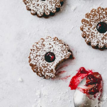 chocolate linzer cookies next to a teaspoon with raspberry jam