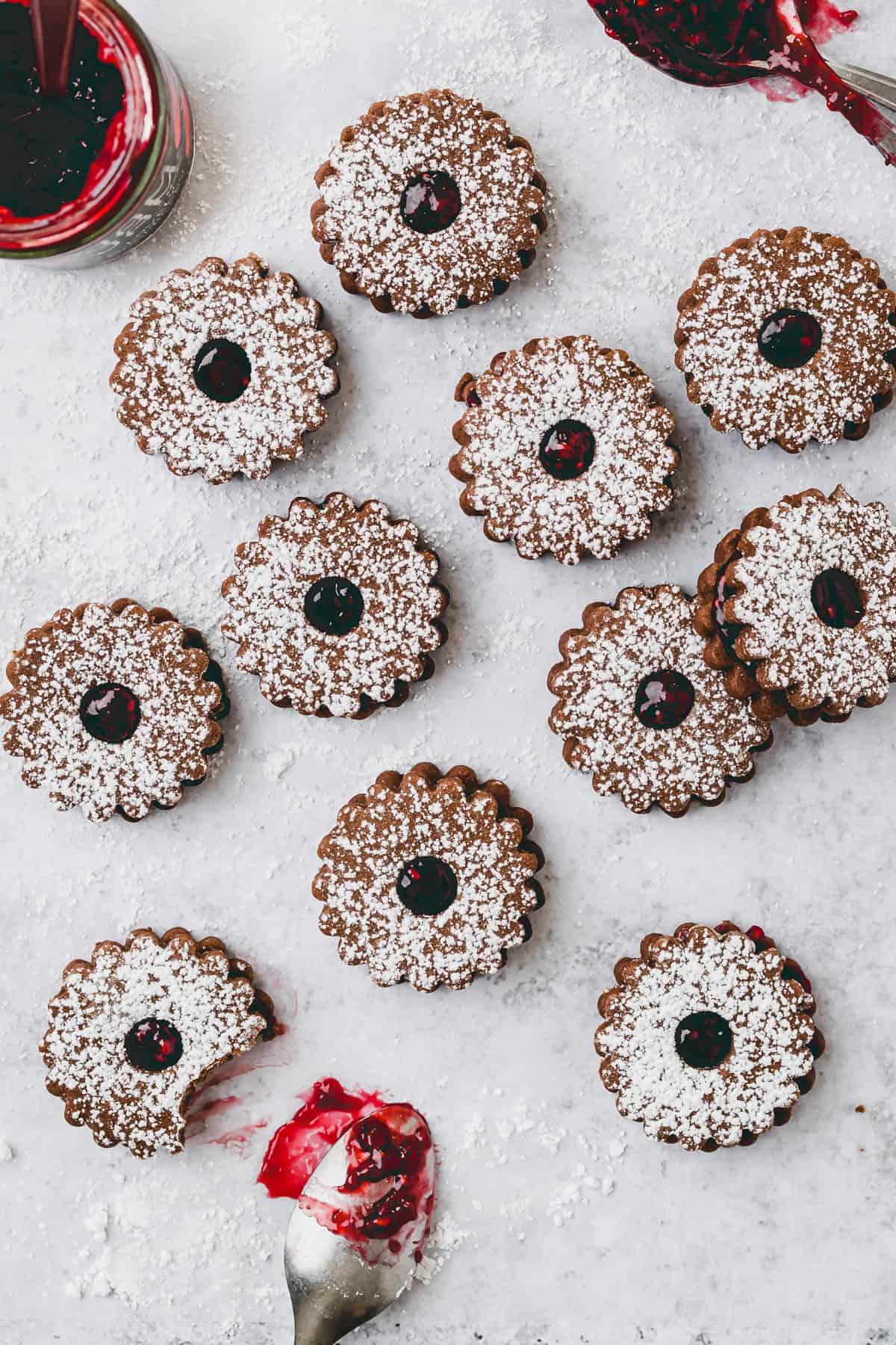 raspberry linzer cookies next to a jar raspberry jam
