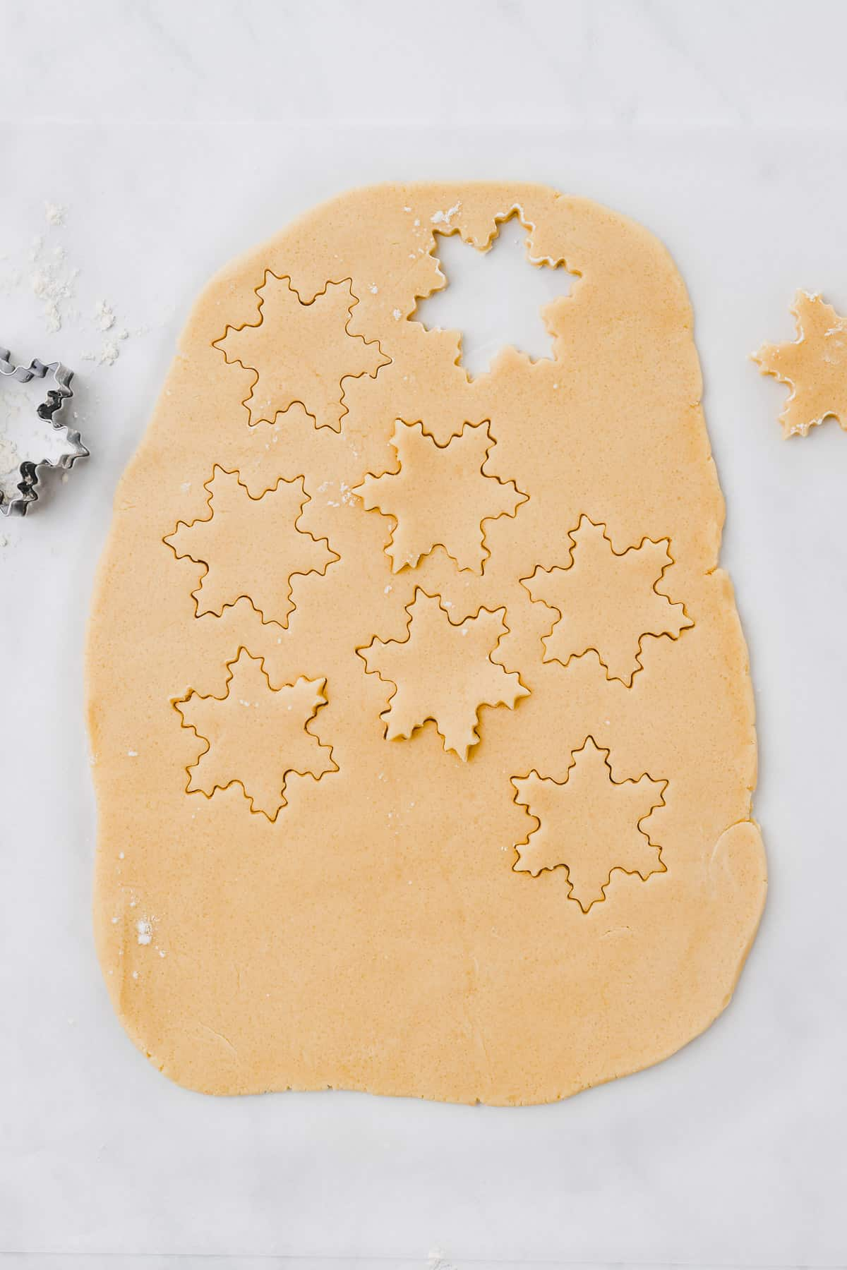 rolled out sugar cookies dough with a snowflake cookie cutter