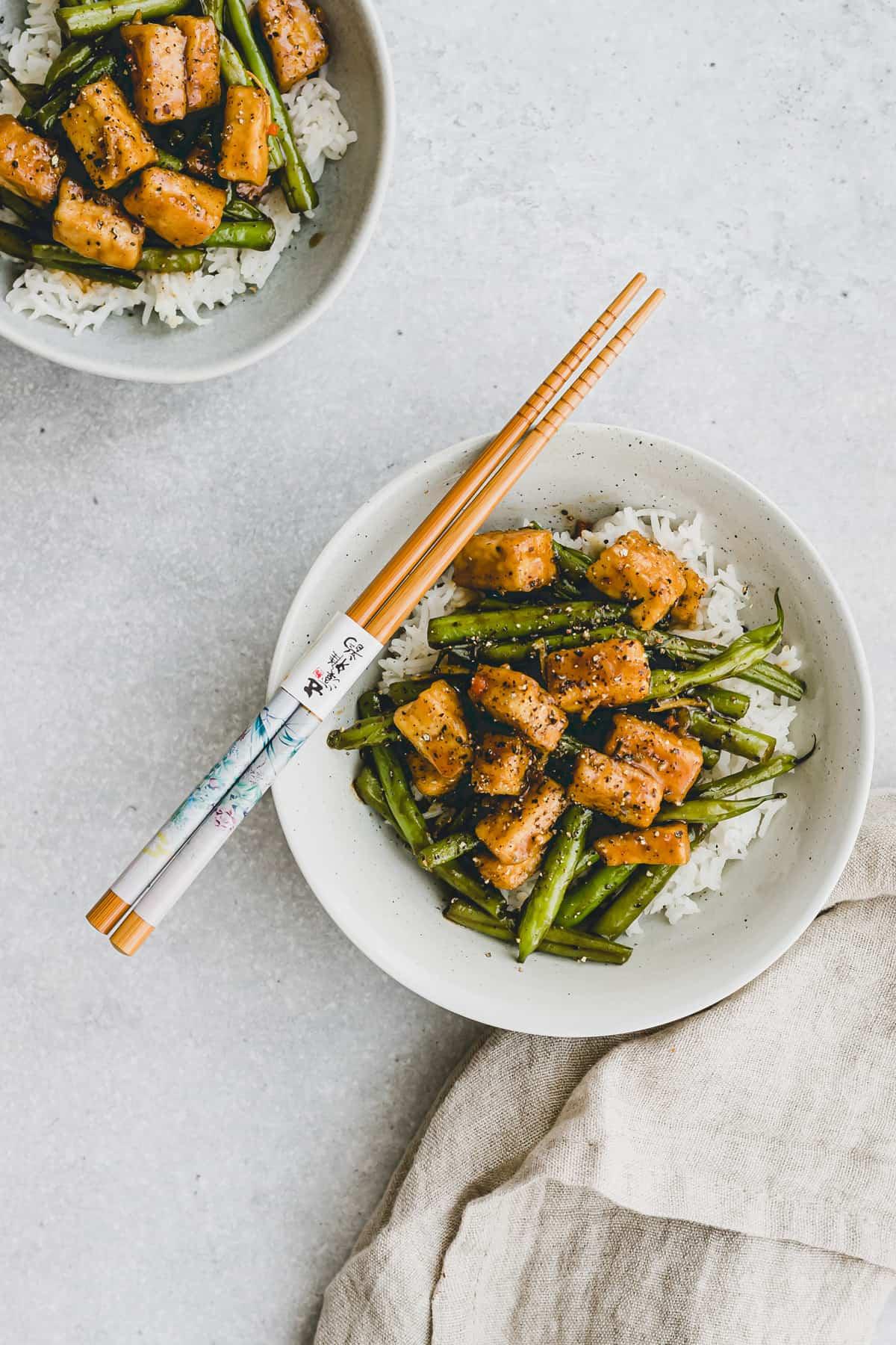 zwei schüssel gebratener tofu und grünen bohnen auf reis
