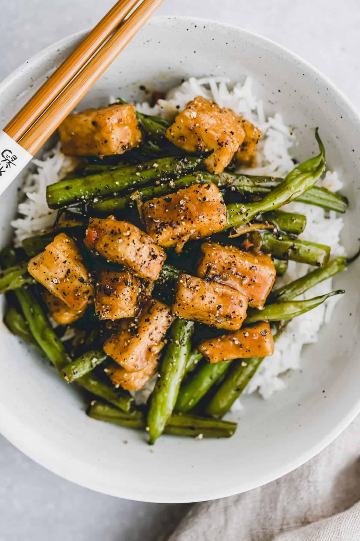 nahaufnahme von black pepper tofu mit grünen bohnen auf reis