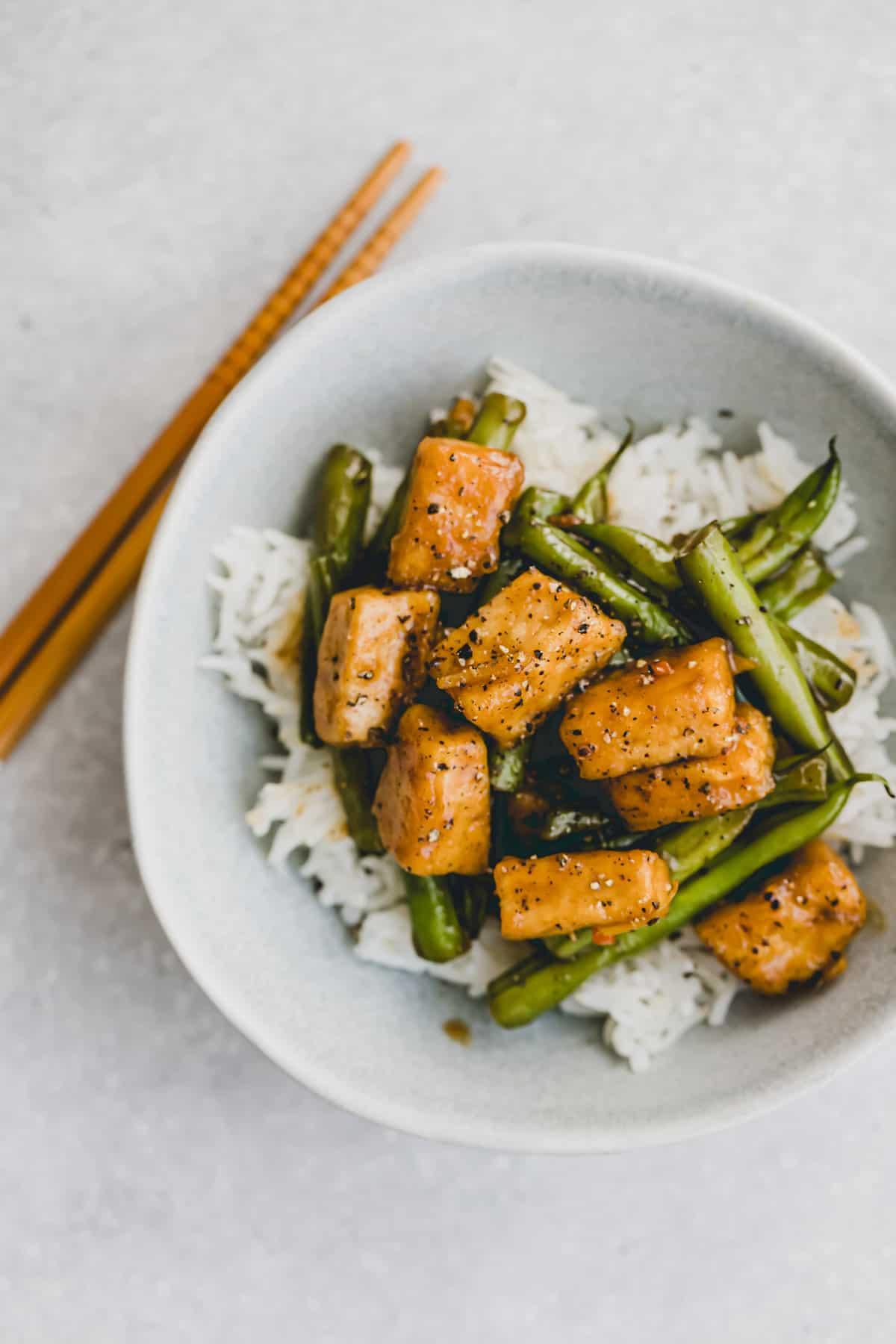 eine schüssel mit mariniertem tofu und grünen bohen