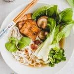 vegane pho in einem suppenteller neben pak choi und frischer minze