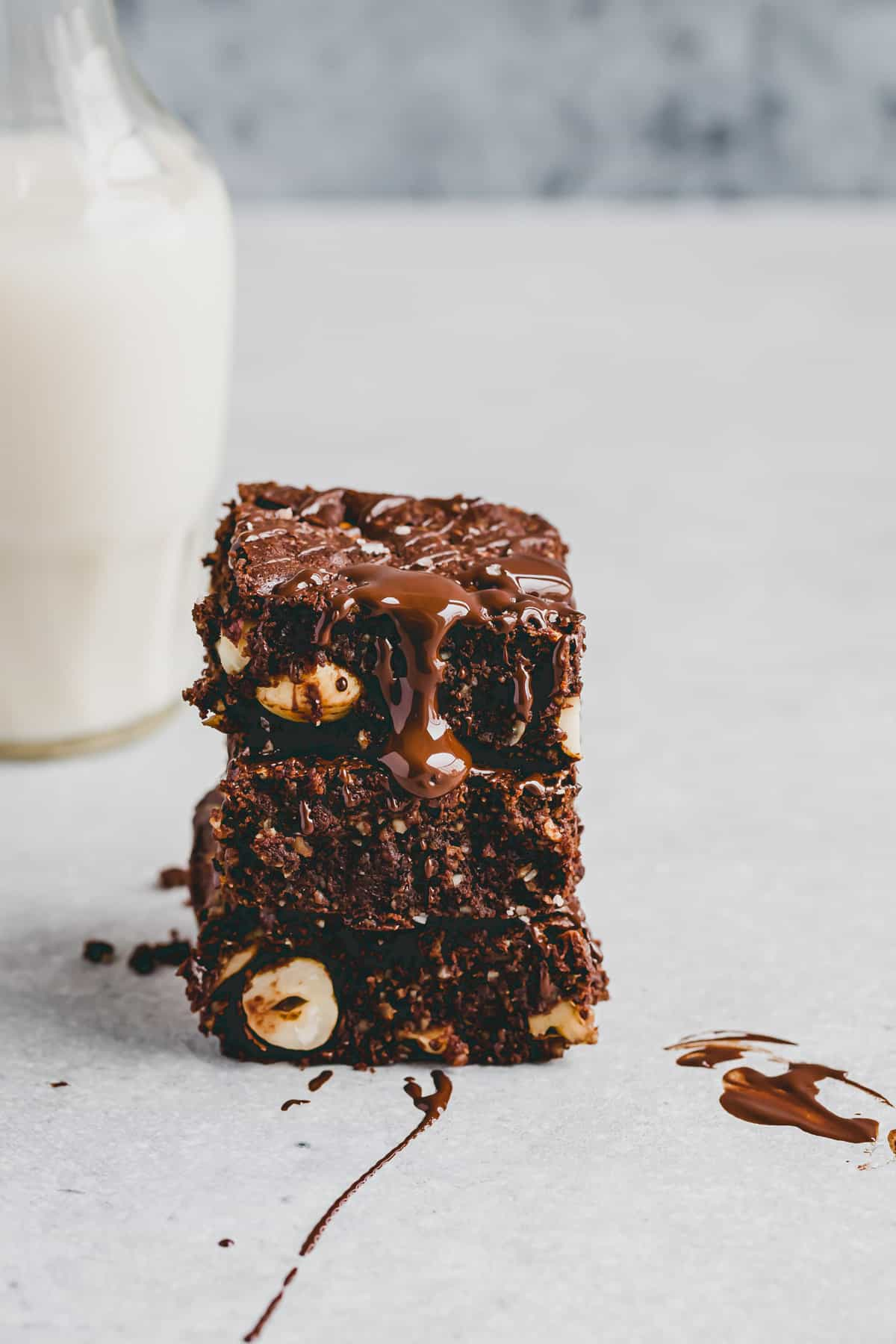 paleo brownies stacked next to a bottle dairy-free milk