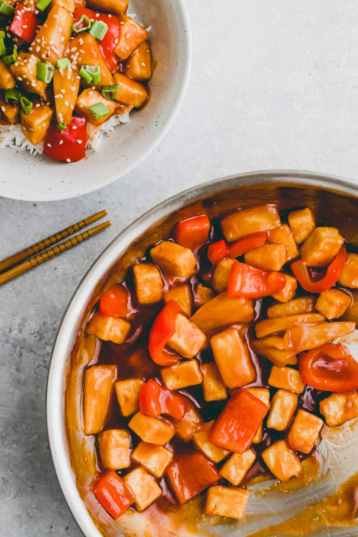 a skillet with vegan sweet and sour sauce tossed with tofu