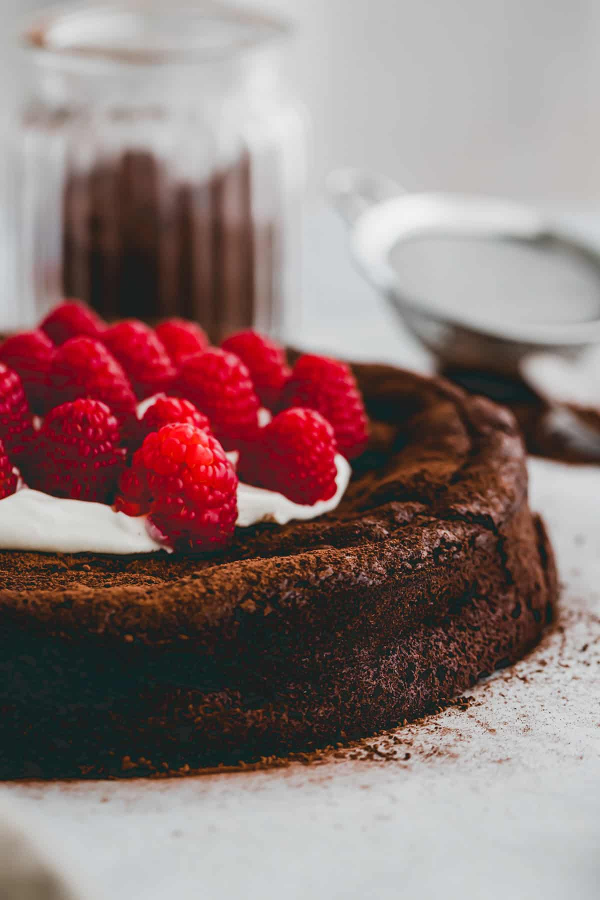 close up shot of flourless chocolate cake with raspberries