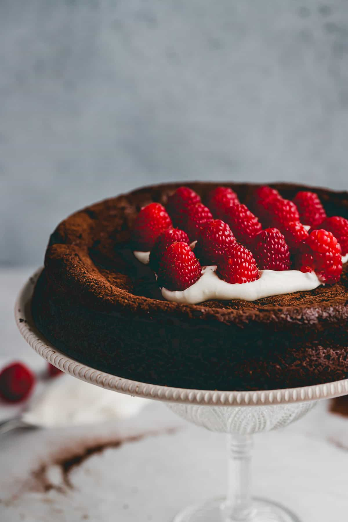 dairy-free flourless chocolate cake on a cake stand