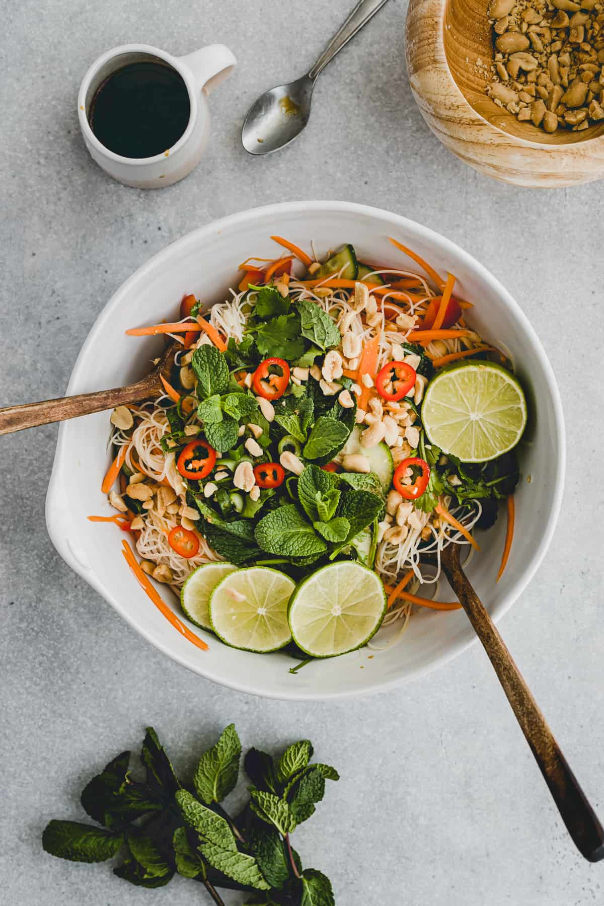 asian vegan vermicelli noodle salad in a bowl next to herbs, dressing, peanuts