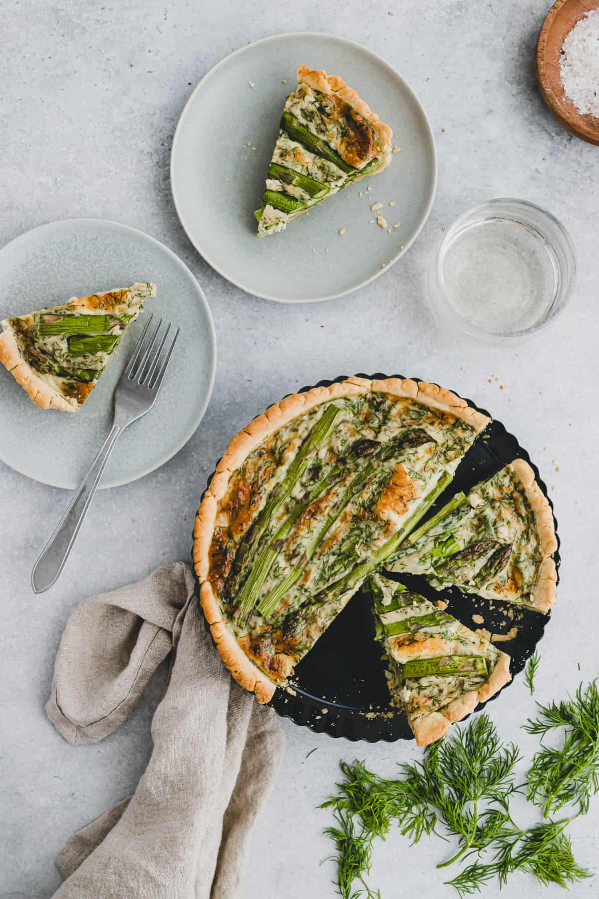 sliced quiche with green asparagus in a quiche pan next to two slices of quiche on a plate