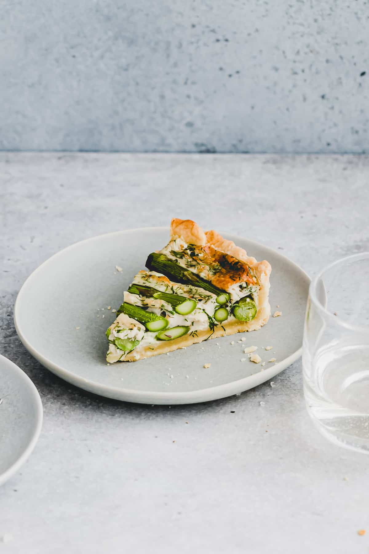 a slice asparagus brie quiche on a blue plate